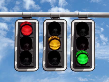 Three traffic lights against blue sky background