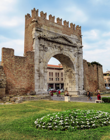 Rimini, Italy - June 14, 2017: Unidentified people walk under Augustus Arch - the ancient romanesque gate and the historical landmark of Rimini, Italy. Editorial
