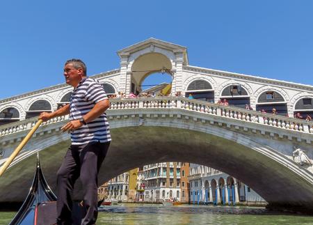 venice: Venice, Italy - June 20, 2017: Unidentified Gondolier in front of the Rialto bridge in Venice, Italy. Venice Grand Canal.