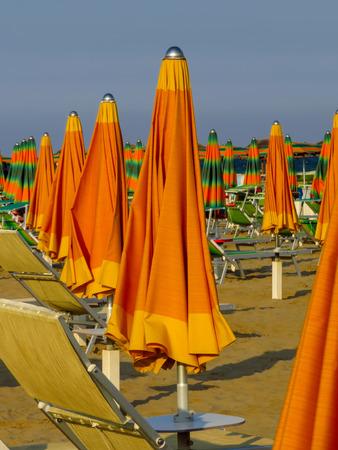 Orange closed umbrellas on the beach of Rimini in Italy Stock Photo