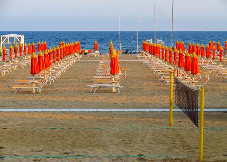 Orange umbrellas and sunbeds on the beach of Rimini in Italy