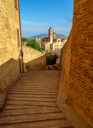 View from old street to Ducale Palace in Urbino city, Marche, Italy