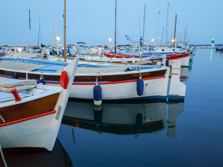Small colorful boats anchored in port in Cannes, France. Night view. Stock Photo