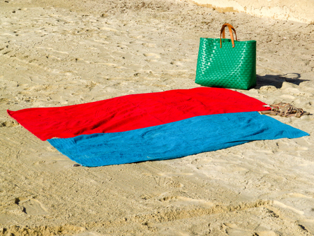 Two towels and beach bag on sand