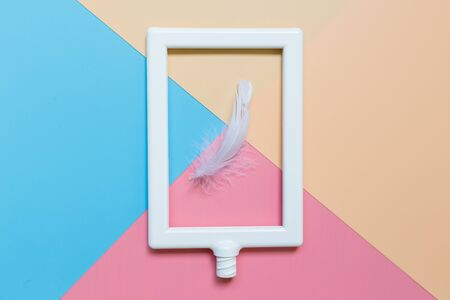 White feather and Photo Frame set on Pastel background Фото со стока