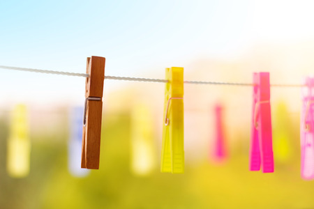 Colorful laundry pegs (clothes pins) hanging on the washing line in spring.