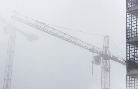 Large crane in a fog building house. 版權商用圖片