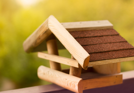 Wooden birdhouse with blurred nature in the background.
