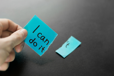 Hand holding motivational sticky paper. No excuses, i can do it.