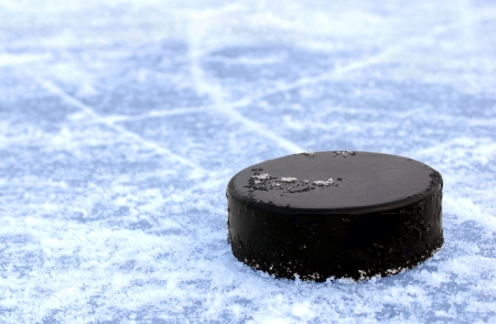 wintrily: black hockey puck on ice rink  Stock Photo