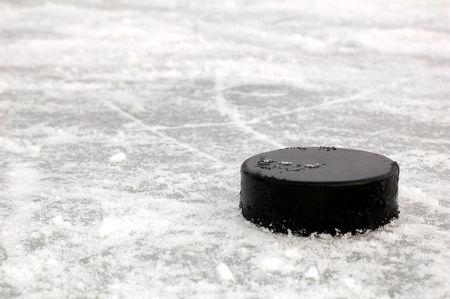 hockey sobre hielo: disco de la negra de hockey en la pista de hielo