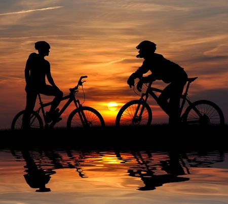 two mountain biker silhouette in sunrise  photo