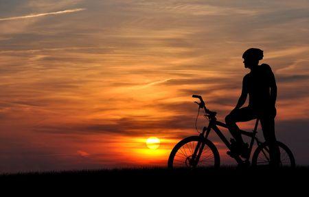 bike race: mountain biker silhouette in sunrise