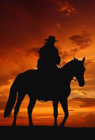 silueta ciclista: silueta de vaquero en la salida del sol  Foto de archivo