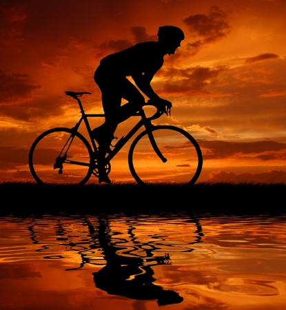 road bike: Road cycler silhouette in sunrise  Stock Photo