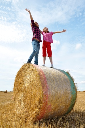 children standing on a bale of straw  photo