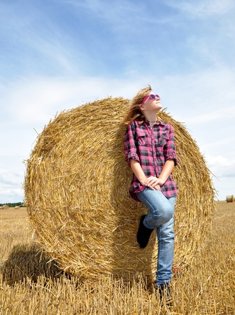 Girl leaning on stack of straw  Stock Photo - 10441420