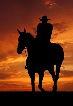 vaquero: Silueta del vaquero con el caballo en la puesta del sol Foto de archivo