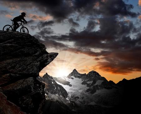 andando en bicicleta: silueta de un ciclista en los Alpes suizos