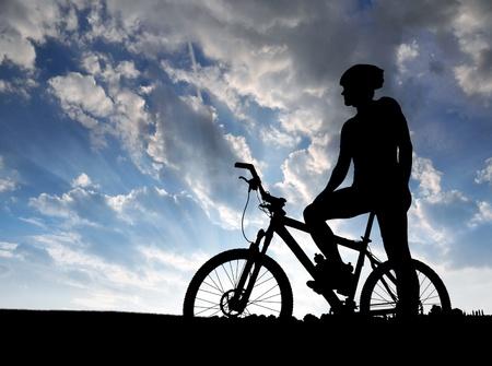 ciclista: montaña silueta del motorista en la salida del sol