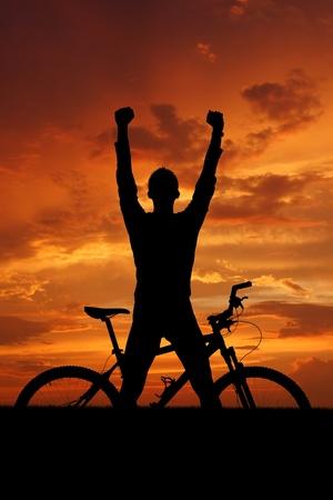 ciclista: monta�a silueta del motorista en la salida del sol