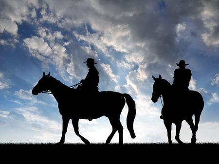 Silhouette cowboys met paarden in de zonsondergang Stockfoto