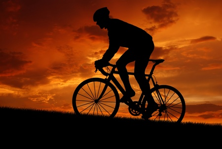silhouette of the cyclist riding a road bike at sunset  photo
