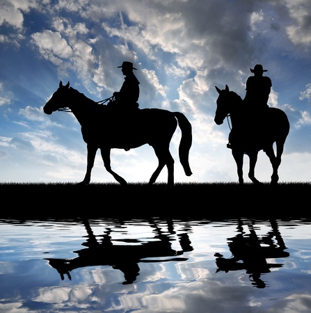 country western: Silhouette cowboys with horses in the sunset