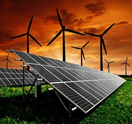 energia solar: Paneles de energía solar y turbinas de viento en la puesta del sol