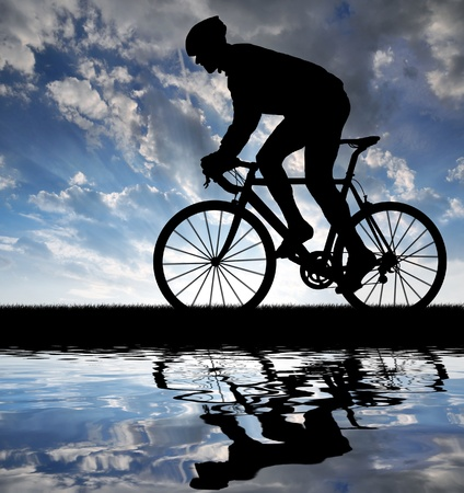 sports race: silhouette of the cyclist riding a road bike at sunset