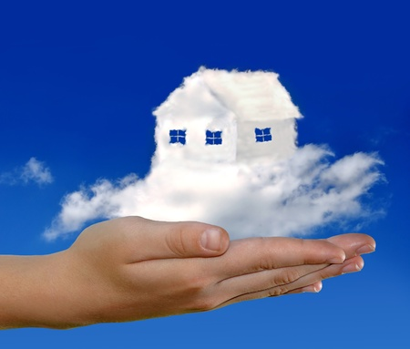 dream home: house from clouds in the hand on blue sky