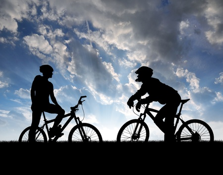 bike race: mountain bikers silhouette in sunset