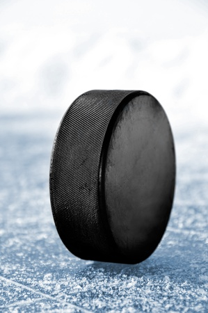 hockey puck: black hockey puck on ice rink
