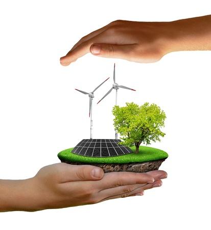 ahorro energia: Pequeña isla con paneles solares y turbinas eólicas en las manos aisladas en blanco Foto de archivo