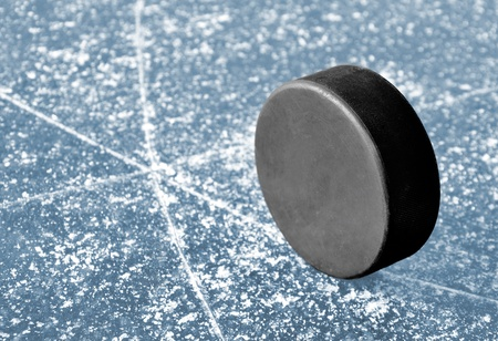 wintrily: black hockey puck on ice rink