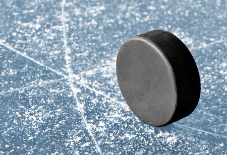 rink: black hockey puck on ice rink