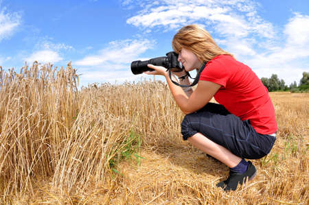 photographing: girl taking photos in wheat field  Stock Photo