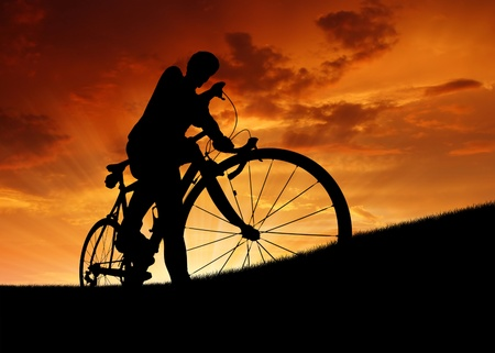 silhouette of the cyclist on road bike at sunset Stock Photo - 12904449