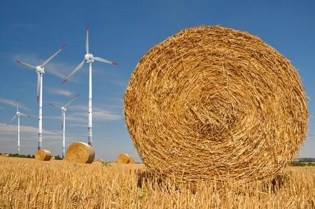Straw bales on farmland with wind turbine  photo