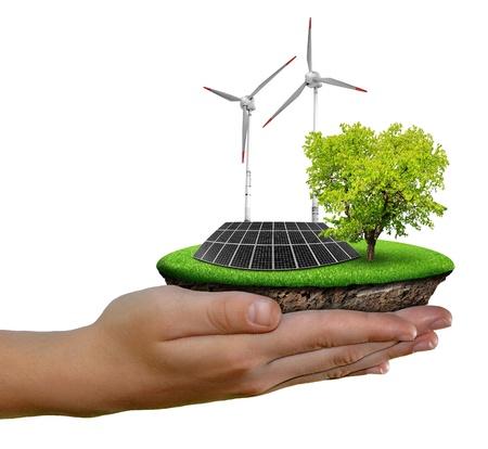 PLACAS SOLARES: Pequeña isla con paneles solares y turbinas eólicas en las manos aisladas en blanco Foto de archivo