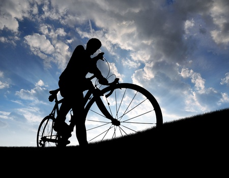 silhouette of the cyclist on road bike at sunset  photo