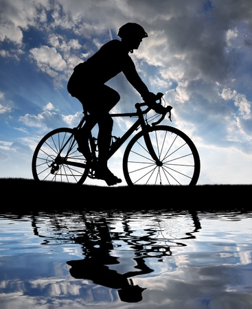silhouette of the cyclist riding a road bike at sunset Stock Photo - 13076404