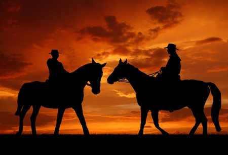 Silhouet cowboys met paarden in de zonsondergang