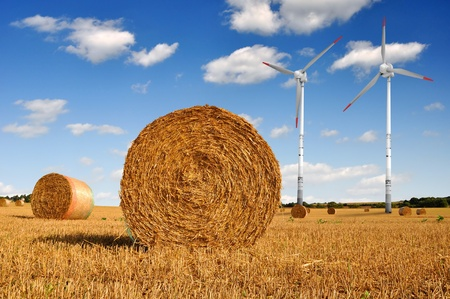 Straw bales on farmland with wind turbine on blue cloudy sky photo