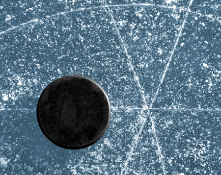 black hockey puck on ice rink Stock Photo - 14126392