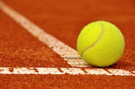 Tenisowa piłka na tenisowym glinianym sądzie