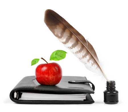 Feather in ink bottle and workbook with an Apple  photo