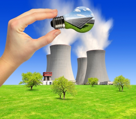 Nuclear power plant and  hand with bulb Stock Photo - 15419878