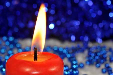 burning red candle on blue christmas bokeh Stock Photo - 15646274