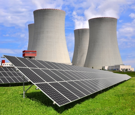 power of savings: Solar energy panels before a nuclear power plant Stock Photo